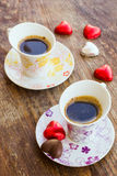 Two cups of coffee with heart shaped candy Royalty Free Stock Image