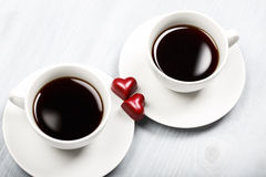 Two cups of coffee and heart shaped sweets Royalty Free Stock Photo