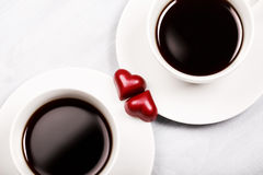 Two cups of coffee and heart shaped sweets Stock Image