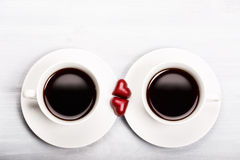 Two cups of coffee and heart shaped sweets Royalty Free Stock Image