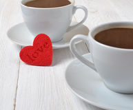 Two cups of coffee and a heart. Stock Photos