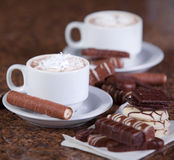 Two cups of coffee or hot cocoa with chocolates and  cookies on Stock Photos
