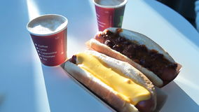 Two cups of coffee and hot dogs. Close-up shot of placing two cups of hot coffee on the table with two hot dogs. Eating in fast food restaurant stock video footage