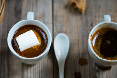 Two cups of coffee with marshmallow and cookie crumbs on a wooden background. Two cups of coffee with marshmallow and cookie crumbs on a wooden background Royalty Free Stock Photos