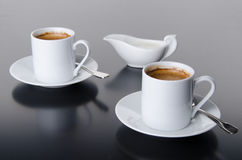 Two cups of coffee with a milk jug Royalty Free Stock Image