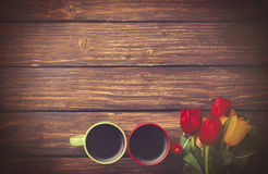 Two cups of coffee near tulips on wooden table. Royalty Free Stock Photography