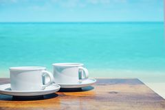 Two cups of coffee over a clear ocean`s water. Two cups of hot coffee over a clear ocean`s water Stock Photo