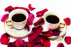 Two cups of coffee in the petals of roses Royalty Free Stock Photo