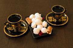 Two cups of coffee and a plate of sweets Royalty Free Stock Photos