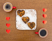 Two cups of coffee, a plate with Valentines Day heart-shaped cakes and red hear Stock Images