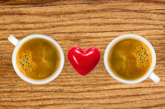 Two cups of coffee and red heart on wooden table Royalty Free Stock Images