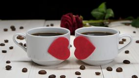 Two cups of coffee for romantic lovers. Slow motion. Two cups of coffee for romantic lovers, valentine day, black coffee in white cups are decorated with hearts stock video
