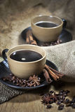 Two cups of coffee with spices. Two ceramic cups of coffee with cinamon and star anise on old coffee jute bugs Royalty Free Stock Photos