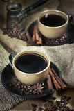 Two cups of coffee with spices. Two ceramic cups of coffee with cinamon and star anise on old coffee jute bugs Stock Photography