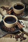 Two cups of coffee with spices. Two ceramic cups of coffee with cinamon and star anise on old coffee jute bugs Royalty Free Stock Image