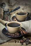 Two cups of coffee with spices. Two ceramic cups of coffee with cinamon and star anise on old coffee jute bugs Stock Image