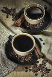 Two cups of coffee with spices. Two ceramic cups of coffee with cinamon and star anise on old coffee jute bugs Stock Photos