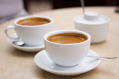 Two cups of coffee and sugar bowl on marble table Stock Photos