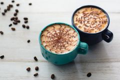 Two cups of coffee surrounded by coffee grain royalty free stock photography