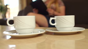 Two cups of coffee on the table, close-up. Two cups of coffee on the background of a girl with a tablet, slow motion stock video