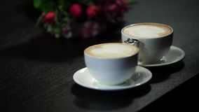 Two cups of coffee on the table, latte art stock video