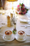 Two cups of coffee on the table. Two cups of coffee on a table and a vase Royalty Free Stock Photos