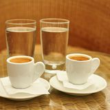 Two cups of coffee and two glasses of water Royalty Free Stock Photo