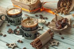 Two cups of coffee in vintage metal cups, a box of halwa, dates, coffee beans, nuts and cinnamon Stock Image