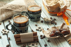 Two cups of coffee in vintage metal cups, a box of halwa, dates, coffee beans, nuts and cinnamon Royalty Free Stock Photography
