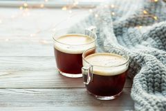 Two cups of coffee, warm knitted sweater on wooden background. Warm lights. Cozy winter morning royalty free stock photos