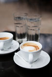 Two cups of coffee and water. Two milk based coffees in white cups and glasses of water on cafe table Stock Photography