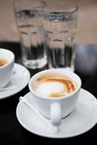 Two cups of coffee and water. Two milk based coffees in white cups and glasses of water on cafe table Stock Image