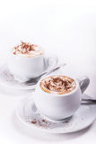 Two cups of coffee with whipped cream. And chocolate on white background Stock Photography
