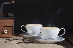 Two Cups Coffee. Two white cups filled with steaming hot coffee with vintage coffee grinder in background Stock Photography