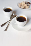 Two cups of coffee on the white table and with two spoons and so. Me sugar Stock Image