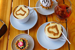 Two cups of coffee, a wineglass of brandy and cake. Are on the table Royalty Free Stock Photo