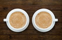 Two cups of coffee on the wooden table Royalty Free Stock Photos