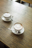 Two cups of coffee on wooden table Royalty Free Stock Image