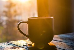Two cups with coffee on the wooden table. Still life with cup of coffee on the carpathian mountains background during the sunset Stock Photos