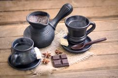 Two cups of coffee on a wooden table. Two cups of coffee with chocolate on a wooden table, spices, foam Royalty Free Stock Photo