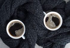 Two cups of coffee wrapped in black woolen scarf Royalty Free Stock Images