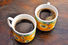 Two cups of coffee. Two yellow cups of coffee on a wooden table Stock Images