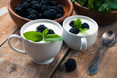 Two cups of creamy yogurt with blackberries Stock Photo