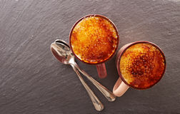 Two cups of creme brulee on a slate board Royalty Free Stock Photos