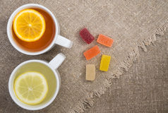 Two cups with different types of tea. Cups of different tea and jellies on the sackcloth Royalty Free Stock Photography