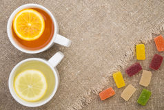 Two cups with different types of tea. Cups of different tea and jellies on the sackcloth Stock Images