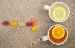 Two cups with different types of tea. Cups of different tea and jellies on the sackcloth Royalty Free Stock Photo