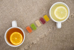 Two cups with different types of tea. Cups of different tea and jellies on the sackcloth Stock Image