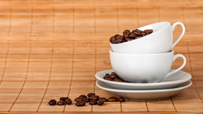 Two cups at each other with coffee grains on the sauce Stock Photo