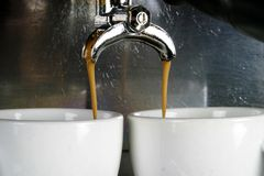 Two Cups Espresso. Detail image of two cups of espresso being made in an industrial profesional machine Stock Photo